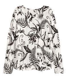 Weiß/Schwarz gemustert. Langarmbluse aus bedrucktem Strukturstoff. Die Bluse hat einen Nackenschlitz mit bezogenen Knöpfen.