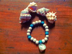 Plumeria White and Blue Wood Bracelet Wood beads and shell charm  Like us on https://www.facebook.com/plumeriajewelry to purchase.