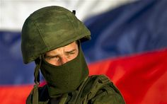 16/3/14 - Crimea referendum. A pro-Russian soldier is back dropped by Russia's flag while manning a machine-gun outside an Ukrainian military base in Perevalne, Ukraine.
