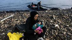 A woman holds her child on shore shortly after arriving with other migrants and refugees on the Greek island of Lesbos after crossing the Aegean sea from Turkey, on October 19, 2015.