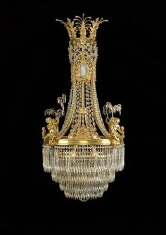 An Important Louis XVI Style Cut-Glass and Gilt-Bronze Mounted Chandelier with Wedgwood Style Porcelain Plaques (Ref: The chandelier contains four putti holding a rod of cut-glass drops, such as the one seen here.