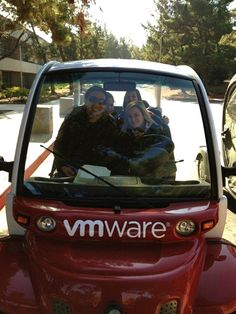 Members of the VMware University Relations Team riding around in a gem car.
