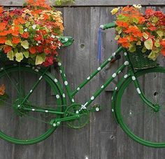 A repainted bike with flower basket base hanging on a wooden fence.