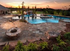 Yukon Estate 2  Luxury Pool with Island and inlaid with glass tile, flagstone patio, natural boulder waterfall, spa and fire pit.