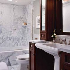 White marble tile, mirrored surfaces, a glass shower wall, and floor-to-ceiling cabinets create the illusion of space in this small-space bathroom. | Courtesy National Kitchen & Bath Association | thisoldhouse.com