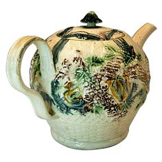 Creamware pottery Teapot by in coloured glazes. Relief moulded decoration typical of the work of William Greatbach of Staffordshire. A well coloured and crisply modelled example. -England, circa 1770 -  John Howard, Woodstock, UK