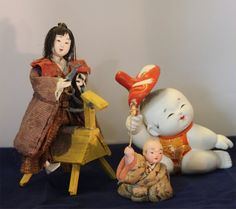 Three dolls in various media showing children playing.  The small baby is 2 inches tall (exclusive of toy).  The boy on a horse is probably 19th century; the boy with a mask dates from the past 30 years or so.