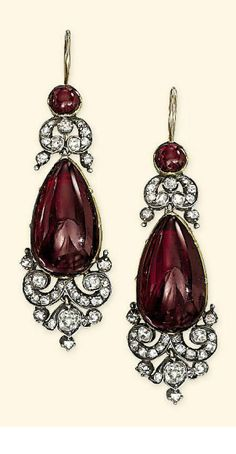 A VICTORIAN GARNET AND DIAMOND DEMI-PARURE Comprising a brooch with garnet cabochon centre within old-cut diamond cartouche-shaped surround suspending a detachable two-stone garnet and and diamond pendant; ear pendants en suite, together with diamond and Victorian Jewelry, Antique Jewelry, Vintage Jewelry, Victorian Era, Jewelry Accessories, Jewelry Design, Garnet Jewelry, Garnet Earrings, Silver Earrings
