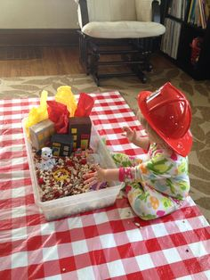 Fire safety sensory bin - red pom-poms, buildings w tissue flames, wooden fire engine, Dalmatian, play fire helmets & pipe cleaner hoses