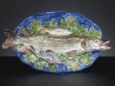A FRENCH MAJOLICA PALISSY STYLE TROMPE L'OEIL PLATTER LATE 19TH CENTURY, SCHOOL OF TOURS, PERHAPS LANDAIS Naturalistically modeled as a large open-mouthed pike and two smaller fish resting amidst a bed of oak leaves on a shaped-oval platter 17½ in. (44.4 cm.) long