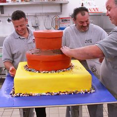 Mauro pats cookie crumbs around the edges of the cake to look like soil in pots while Joe and Danny use candy rocks to really give the New York Botanical Garden cake some life. #CakeBoss