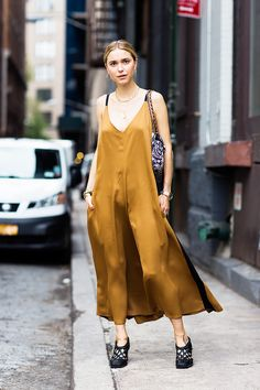 Pernille Teisbaek wears a silk Céline slip dress with woven heels, gold jewelry, and a Chanel shoulder bag