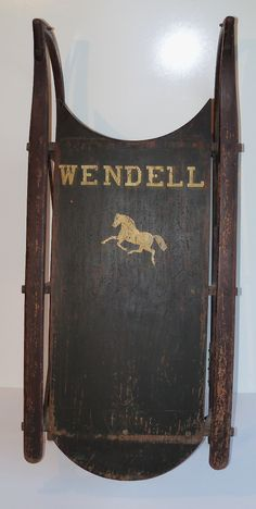 """WENDELL'S SLED  This is a nice sled with a child's name and a trotting horse stenciled in gold paint on the oxidized green board with red side bars and runners.  Approximately 3"""" of the end of one wooden runners has been replaced some time ago. The sled is unmarked and was found in coastal Maine.  It dates to approximately 1880. 14 3/4"""" wide x 31"""" long.  $450."""