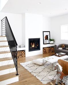 Cozy minimal style home with bright, white walls, fireplace, and patterned rug