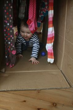Create a baby play tunnel from a cardboard box and tights for sensory play and gross motor skill development!
