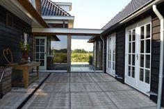 Doorgang tussen huis en bijgebouw van glas