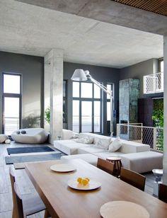 intérieur moderne avec mobilier industriel, plafond en béton et habillage de cheminée original en bleu