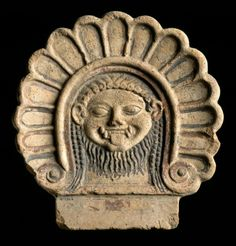 Antefix (roof ornament) of terracotta painted in black and red, depicting the head of a gorgon within a border of palmettes: Ancient Mediterranean, Italian, believed to have been found in Capua, Etruscan, 6th century BC, c.550 BC © National Museums Scotland