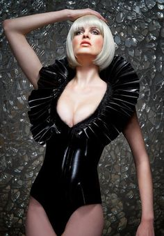 Black latex body suit with huge standing collar. The part of collar at the back of the neck is supported by boning. Front zip opening.