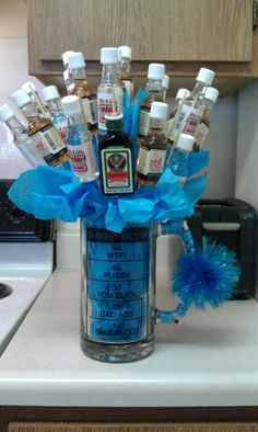 "Alcohol Bouquet that I made for my boyfriends 21st!!!:):) You will need: one giant mug, tissue paper and sterofome ball to stick inside, wooden kabob sticks, tape, and your choice of 21 ""airplane shots"" I am in love with this :) I got my Chug-o-Meter cup from Spencers, BTW."