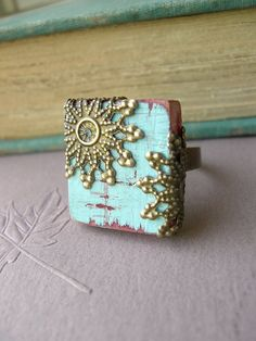A Scrabble tile is mounted on an antiqued brass band. The tile has been painted with a lovely turquoise shade and aged to give it a vintage feel. There antiqued brass stampings bring texture and depth to this ring and also adds a classic look.
