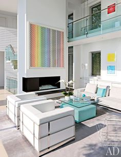 A monoprint by Polly Apfelbaum is displayed above the fireplace in a minimalist home East Hampton home.