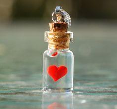 Heart in tiny bottle charm.