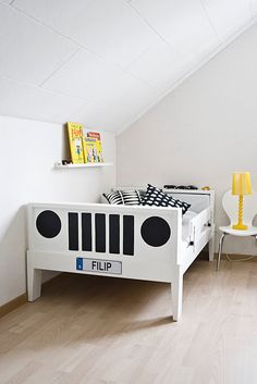 Ikea bed turned into a jeep. I love the chair used as a nightstand.