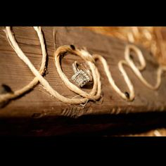"""Wedding rings nestled on barn board in the center of the word """"LOVE"""" written with string! What a great idea for a #WesternWedding"""