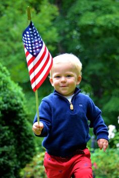 USA, little boy in red white & blue carrying a  the flag