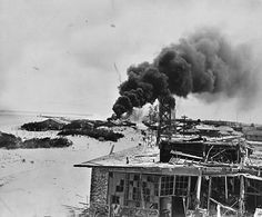 Smoke rises from burning buildings after Japanese air forces attacked the U.S. Navy base at Midway Atoll during the Battle of Midway, June 1942.