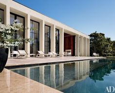 """The rear elevation. """"The muscular stucco colonnade protects the delicate steel-and-glass windows and doors from wind and storms,"""" says Haverland. Richard Schultz outdoor furniture 