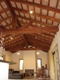 Falso techo decorado con vigas de simil madera y for Cielorrasos de casas
