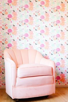 Flower wallpaper and plush pink armchair in reading nook