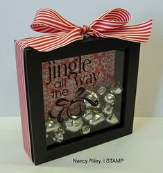 Jingle All the Way (or other saying) Shadow Box gift.   Materials:   Shadow Box  Printed scrapbooking paper or cardstock  Ribbon, craft jingle bells  Transfer sayings/pictures decals  (scissors, glue, edge of credit card or something like to transfew decal).
