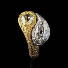 Unusual double-headed snake ring, its yellow gold and platinum body with scale-like engraved decoration and eah snake-head terminal set with a pear-shape diamond, one white and one yellow Hancocks, contemporary
