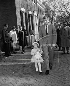 """President-elect John Kennedy and his three-year-old daughter Caroline leave their Georgetown home on the way to church, on Nov. 27, 1960. It was Caroline's third birthday and a small crowd of well-wishers called """"Happy Birthday"""" as she walked with her father in warm, sunny weather. After Kennedy visited his wife and their new son, John Jr. at Georgetown Hospital in Washington D.C. (AP Photo/Byron Reynolds)"""