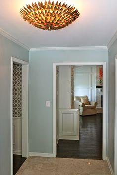 soft aqua wall, painted fireplace brick, wood mantel, tile floor next to hardwood floor