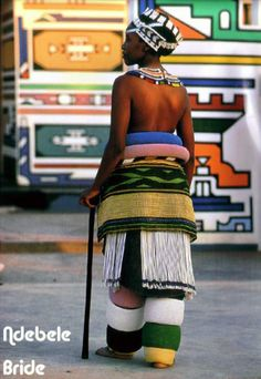 Africa | Having taken off her 'nguba' (blanket), an Ndebele bride dresses in the beaded leg and waist hoops and skirts that constitute her bridal outfit. These hoops, called 'golwani', are made from hanks of twisted grass wrapped in strands of glass beads. They are associated particularly with costumes worn by girls of marriageable age who have completed their initiation into womanhood. || © Angela Fisher & Carol Beckwith; African Ceremonies