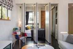 מבט מהסלון לחדר השינה, שביניהם מפרידות שלוש מחיצות לבנות (ומבודדות אקוסטית). אפשר לסגור אותן ולהפריד בין החדרים, או לפתוח ולהסיט אותן הצידה, כך שנוצר מרחב פתוח ( צילום: אביב קורט )