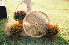 Outside décor with flowers, hay bales, and wagon wheel