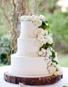 Traditional white round wedding cake with cascading flowers