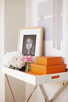 Hallway boasts a white lacquered tray table filled with pops of orange, stacked Hermes Boxes, flowers and Kate Moss photo under a purple and gray abstract piece. Interior Design Inspiration, Home Decor Inspiration, Hermes Home, Hippie Stil, Hermes Orange, Bachelorette Pad, Vintage Box, Tray Decor, Home Staging
