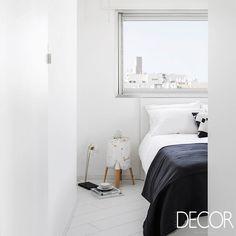 Madeira e detalhes em tom preto contrastam com o branco que impera neste acolhedor dormitório