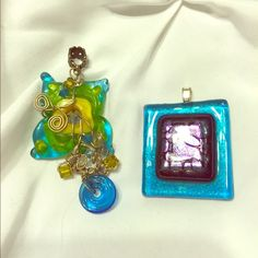 Glass pendants Hand made glass pendants. The left one is yellow, green and Aqua with beads and silver wire embellishments. The right is Aqua with a purple and black dichroic center. Priced for the pair, but can be separated. Smoke and per free home. Jewelry Necklaces