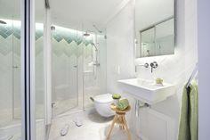 В общей ванной освещение проработано также тщательно как и во всей квартире. В районе умывальника свет идет из-под шкафчика с зеркальным фасадом, а в душе верхнее освещение стены подчеркивает  изменение цвета плитки. .