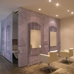 Ghostly images of building facades decorate hanging fabric screens in a beauty salon in Omiya, Japan by Takara Space Design