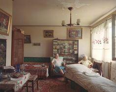 Dieses Einzimmerappartement beherbergt gleich zwei Generationen. Mutter und Tochter wohnen zusammen im zweiten Stock. Gemälde in goldenen Rahmen und rote Teppiche dominieren den in die Jahre gekommenen Raum.