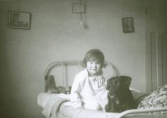 Printed black and white photograph of ER and her pet dog Reme seated on a bed in ER's bedroom in her childhood home at 42 Wood Vale, London N10. This is a copy of the original photograph, which was taken by an unidentified photographer in June 1948. This is one item in the Documenting Homes collection (750/2012-1 to -70).