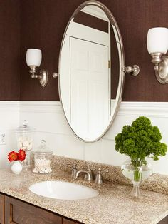 Elegant oval mirror with Satin-nickel light fixtures on either side.... adding softness to the room